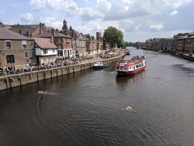DANGEROUS: Two men cross the Ouse, with a riverboat heading towards them