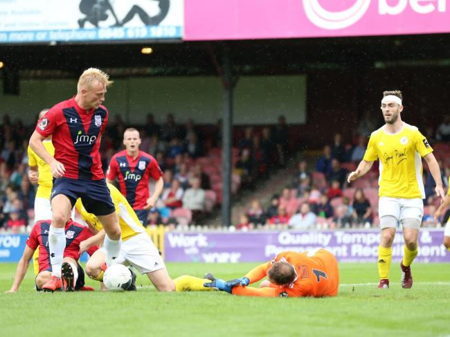 York City's Jordan Burrow can't take advantage of Brackley Town's Danny Lewis spilling the ball in Saturday's game at Bootham Crescent. Picture: Gordon Clayton