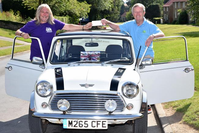 Ian Hughes, left, a member of North Yorkshire Minis, hands over a cheque to Rob Davies, of Ryedale Special Families    Picture: Frank Dwyer