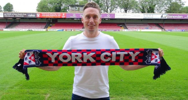 Former York City defender Daniel Parslow poses with the club's flag at Bootham Crescent. Picture: Henry Valantine