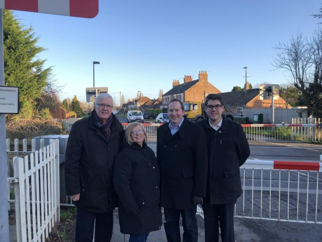 Lord Shipley, Honorary Alderman Ann Reid, Councillor Keith Aspden and Councillor Ed Pearson at the level crossing by the site of the former station in Haxby