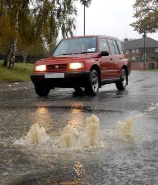 A car negotiates a flooded road in Water Lane, Clifton, following torrential rain in York.