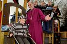 The Bishop of Selby, the Right Rev Martin Wallace, watches as Jay Wright enjoys the new playground