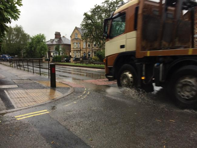 Wet weather in York this morning, as a lorry splashes through puddles in Cemetery Road