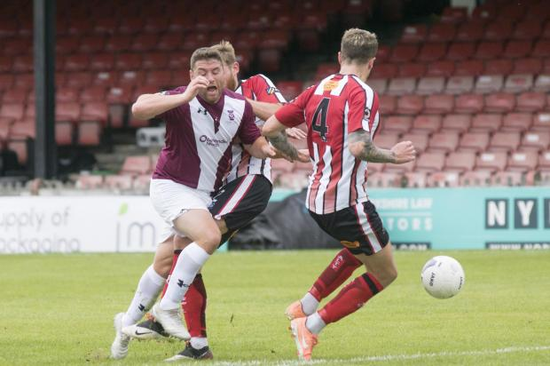 York Press: City's loanee Adam Buxton is halted from advancing into the box by Altrincham's Andy White and Toby Mullarkey