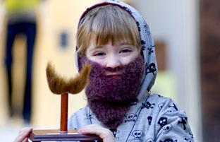 A youngster dons a fake beard and holds the Jorvik Viking Festival's best beard competition trophy