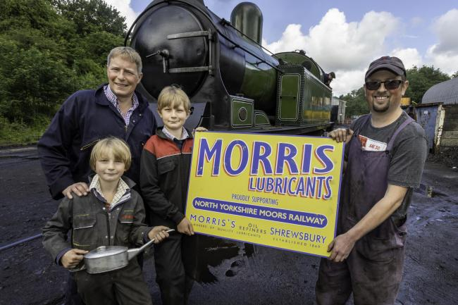Morris Lubricants' executive chairman Andrew Goddard (left) and his sons, William and George, present a sign to Paul Middleton, traction and rolling stock manager at the North Yorkshire Moors Railway