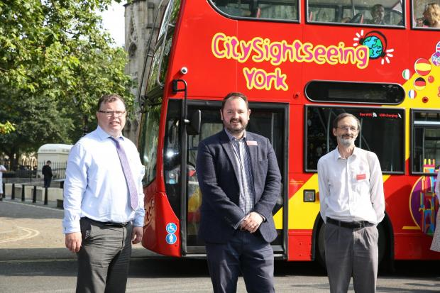 Councillors Andrew Waller, left, and Andy D'Agorne, right, join Transdev CEO Alex Hornby to welcome the new CitySightseeing York tour buses to the city.