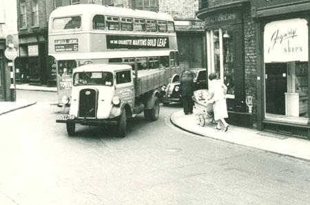 Whip-Ma-Whop-Ma-Gate believed to be between 1953 and 1955. The shop on the right that no longer exists was Joyway Shoes, The bus was a number 5 heading for Dosworth Avenue, and the truck was a vehicle owned by T. Belt & Sons Ltd, St. Maurice's Road, York
