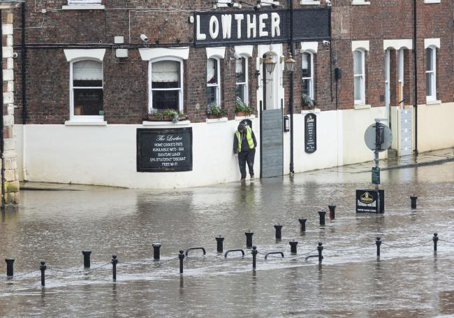 A man tries to walk along a footpath which has been flooded by the River Ouse, in York. The River Ouse, in York, North Yorks, bursts its banks as Storm Christoph hits the UK, pictured in York, NorthYorks, January 19 2021.
