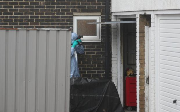York Press: A forensic officer photographs a garage next to a house in Freemens Way in Deal, Kent