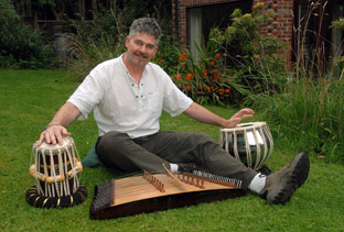 Christian Vassie in his garden with some of the instruments he used for the new Bangladeshi TV series, Bishaash