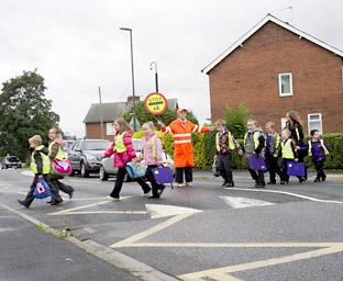 Lollipop lady Janice Sheller guides youngsters from Selby Community Primary School across the road
