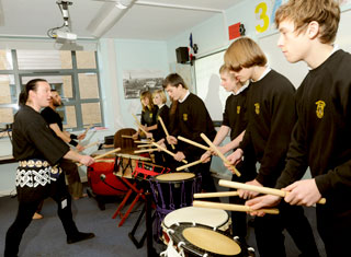 Jared Hardwick, left, of Kaminari Japanese drumming group, works with students at Fulford School during their alternative curriculum day in the language department