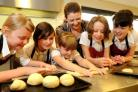 Teacher Emma Acaster rolling out dough with Heworth Primary School pupils.