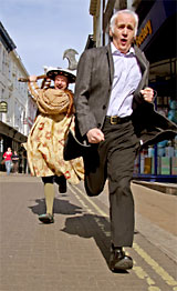 Horrible Histories author Terry Deary being chased by one of his favourite characters, Henry VIII (played by Charles Davies), on his way to a book-signing at Waterstones, in York