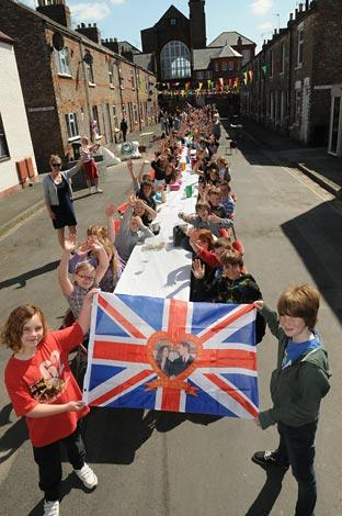 Park Grove School pupils Nina and Ryan fly the Royal Wedding flag as the school sits down for its street party