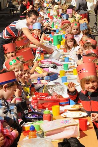 Park Grove School pupils sit down for the street party as teacher Elaine Ramli pours the orange juiice.