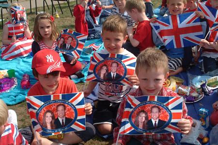 Young pupils at Escrick school  wave their flags in celebration of the royal wedding at the picnic in the school grounds.