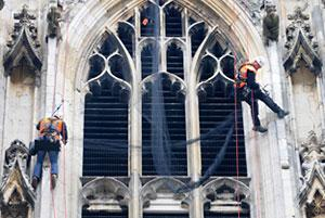 ork Minster maintenance staff abseil into position to install the anti-pigeon netting