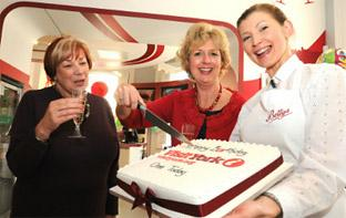 Nora Stead, left, the 450,000th visitor to the Visit York Information Centre helps Gillian Cruddas, chief executive of Visit York, and Bettys Tea Rooms' waitress Barbara Kopytek, to celebrate the centre's first birthday