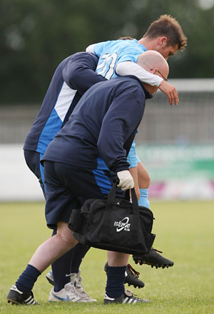 David McDermott is helped off the pitch by physio Jeff Miller