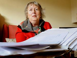 Christine Hutchinson, who is unhappy about treatment from her GP, with a bulging file of  letters and documents relating to her case