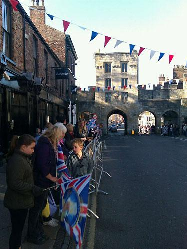 Crowds lining barricades already excitedly awaiting Her Majesty