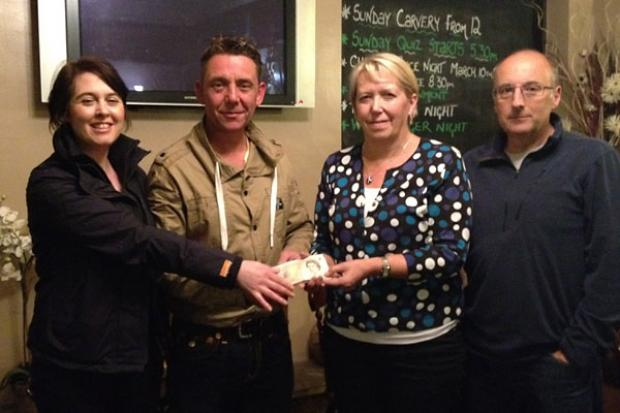 Quiz organiser Helen Powell and landlord Sean Singleton are pictured with Dilys and Chris Hart, the parents of Marine David Charles Hart