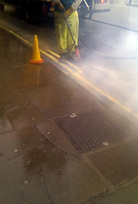 A workman burning off one of the yellow lines