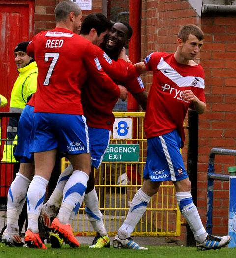 Goalscorer  Adriano Moké is mobbed by team-mates, including debutant Reece Kelly