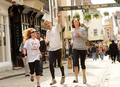 Chris Acton and Mags Hearnden, left, of York On The Run take Linda Harrison along Stonegate during  their jogging tour through the streets of York