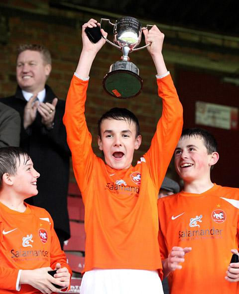 Alex Cowes lifts the trophy after scoring two goals