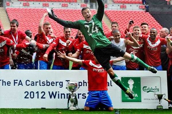 Goalkeeper Michael Ingham leads the after match celebrations after their win against Newport County