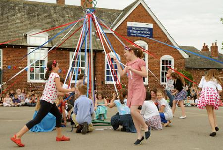 Children dance round the maypole during the Diamond Jubilee celebrations at Dringhouses Primary School