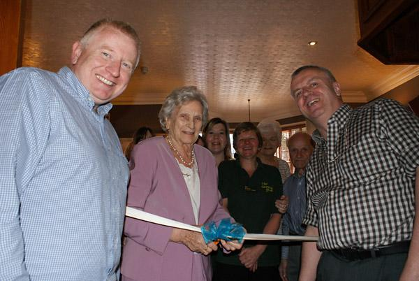 Dorothy Savage cuts the ribbon to open the new Savages Bar, flanked by Gordon Hulme (left) and right David Barritt, the new owners of The Groves hotel