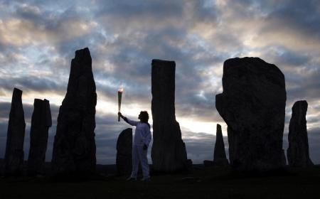 Kirsty Wade holding the Olympic Flame at the Calanais Standing Stones in Callanish as the sun rises on Day 24 of the London 2012 Olympic Torch Relay...