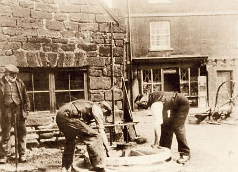 Wheelwrights retyre a wheel