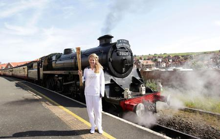 Kelly Williams standing in front of the steam locomotive The Green Knight, holding the Olympic Flame before its journey on the North Yorkshire Moors Railway, from Whitby to Pickering