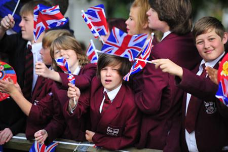Local schoolchildren wave Union Jack flags as they support the Torch Relay on Day 32 of the London 2012 Olympic Torch Relay.