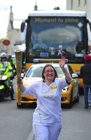 Louise Gutherie carries the Olympic Flame on the Torch Relay leg between Monk Fryston and Tadcaster.