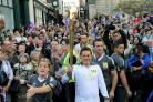 Luke Young carries the Olympic torch along Shamble