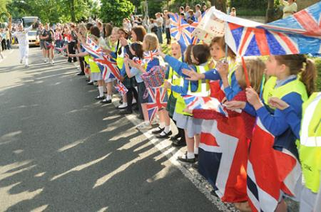 Crowds watch the Olympic Torch passing along Tadcaster Road