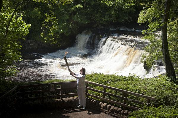 Torchbearer Lucy Gale poses with the Olympic Flame in front of Aysgarth Falls earlier today