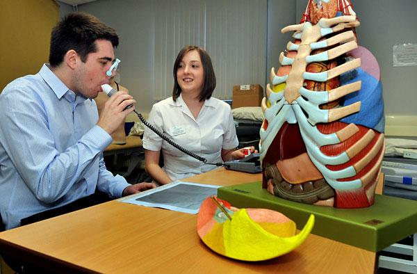 Natalie Keightley instructs graduate Ben Selby in how to use the free lung test monitor at York St John's University