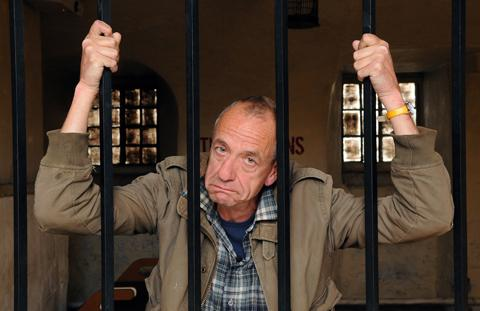 Comedian Arthur Smith behind bars.