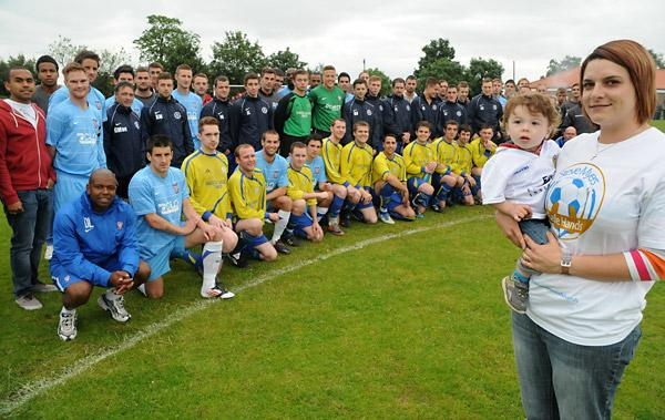 Vicki Myers and son Toby, 16 months, with players who took part in the friendly match in memory of Vicky's late husband and Huntington Rovers player Steve
