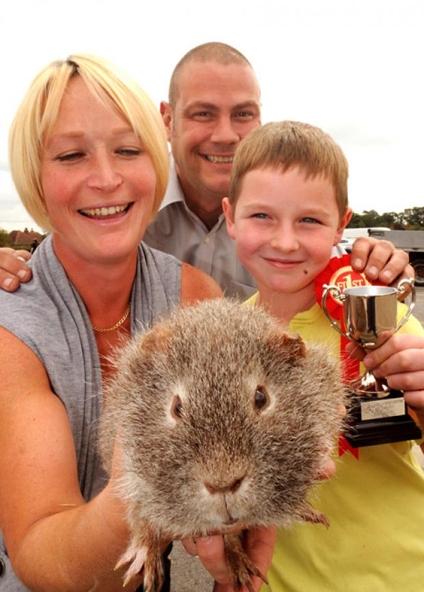 Ciaran Greer and his mum, Jill, with Stripe the guinea pig, which won first prize in last year's small animals category of the Thompson's pet show. Also pictured is Neal Elliott, the manager of Thompson's Country Store at Murton