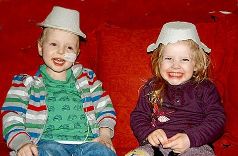 Jamie Inglis and his sister, Poppy, wear bed pans as hats as they share a joke during a hospital visit. But Jamie's father has criticised the NHS's decision not to fund the next stage of his son's treatment.