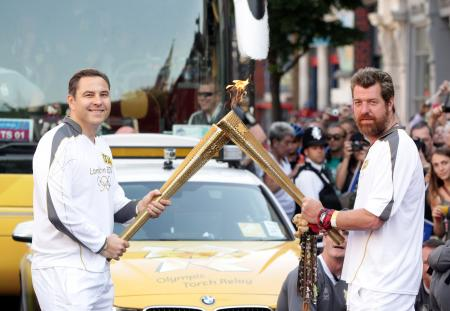 Torch Relay between Islington and The City of London: David Walliams passes the Olympic Flame to fundraiser Phil Packer, who suffered severe spinal injuries while on active service in Iraq...